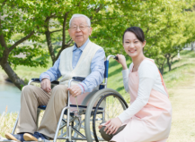 elder male in wheelchair and staff